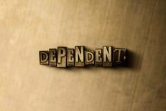 DEPENDENTE - o close-up do vintage sujo typeset a palavra no contexto do metal imagem de stock royalty free