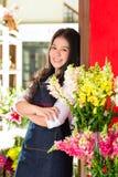 Dependienta asiática en una floristería Fotos de archivo libres de regalías
