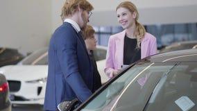 Dependienta en chaqueta rosada discutir el coche con los clientes que se colocan cerca del automóvil y que miran dentro a través  almacen de video