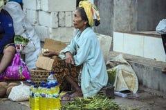 Dependienta en el mercado, pueblo Toyopakeh, Nusa Penida 17 de junio Indonesia 2015 Imagen de archivo libre de regalías