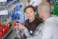 Dependienta joven encantadora en delantal con las herramientas en supermercado imagen de archivo