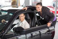 Dependienta que vende un coche al cliente feliz foto de archivo