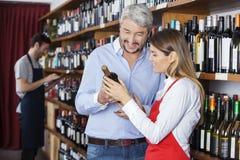 Dependienta Showing Wine Bottle al cliente en tienda Fotografía de archivo libre de regalías