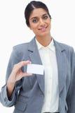 Dependienta sonriente que muestra su tarjeta de visita en blanco Imagen de archivo