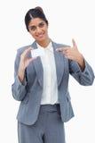 Dependienta sonriente que señala en la tarjeta de visita en blanco Fotografía de archivo libre de regalías