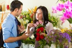Dependienta y cliente en floristería Fotos de archivo libres de regalías