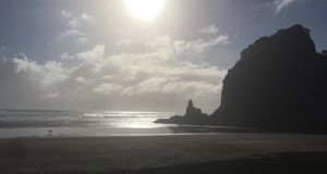 Walking the beach in New Zealand at sunset. Depicting the popular romantic walking the beach at sunset at Piha, New Zealand Stock Photo