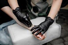 Depilação fêmea da mão Conceito da beleza - pasta do açúcar ou para encerar o mel para o cabelo que remove com as mãos pretas das imagem de stock royalty free