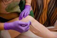 Depilação fêmea da mão Conceito da beleza - pasta do açúcar ou para encerar o mel para o cabelo que remove com as mãos pretas das fotos de stock royalty free