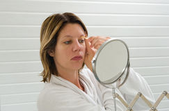 Depilating the eyebrow. A woman is looking in the mirror while she is depilating her eyebrow royalty free stock photography