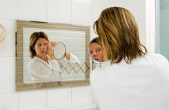 Depilating the eyebrow. A woman is looking in the mirror while she is depilating her eyebrow royalty free stock image