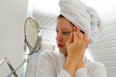Depilating the eyebrow. A woman is looking in the mirror while she is depilating her eyebrow stock photos