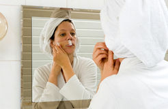 Depilating her moustache. A woman is depilating the small hairs from her moustache in front of a mirror stock photos