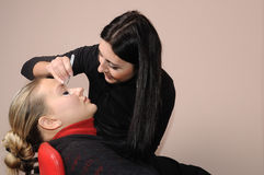 Depilating a woman's eyebrows. Beautician depilating a woman's eyebrows with tweezers stock photography