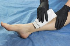 Depilation female legs and hands in a beauty salon