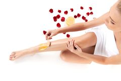 Depilation of female legs with waxing on white background. Top view of woman getting legs waxed for hair removal near scattered petals Royalty Free Stock Photos