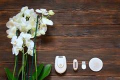 Depilator des elektrischen Rasierapparats mit orhides auf dunklem hölzernem Hintergrund Lizenzfreies Stockfoto