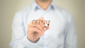 Deploy, Man writing on transparent screen Stock Photos