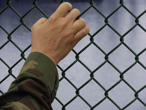Deployed. American soldier's hand on fence with clipping path royalty free stock photography