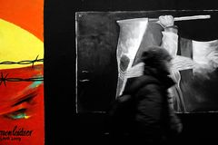 Deployment. Berlin, Germany-January 02, 2012:  The Berlin Wall when it rains. A man with a hooded rain jacket crossing a painted image of the East side gallery Stock Photos