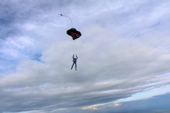 The deployment of parachute in the sky. Parachute is deploying in the cloudy blue sky. Skydiver is gripping lines royalty free stock photography