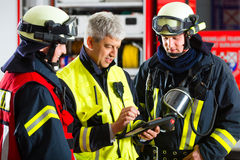 Deployment planning on Tablet-Computer. Fire brigade - Squad leader gives instructions, he used the Tablet Computer to plan the deployment Royalty Free Stock Photo