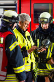 Deployment planning on Tablet-Computer. Fire brigade - Squad leader gives instructions, he used the Tablet Computer to plan the deployment Royalty Free Stock Images
