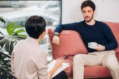 Deponuje pieniądze pracownika konsultuje przystojnego mężczyzny w biurze zdjęcie stock