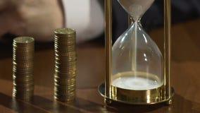 Deponuje pieniądze pracownika kręcenia hourglass na stole, biznesów projekty dochody, czas projekcji zbiory wideo