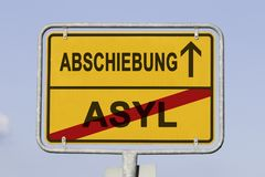 Deportation ahead in german. Yellow road or town sign informing in german that asylum is behind and deportation is ahead. Concept for national separation policy royalty free stock image