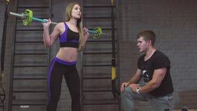 Deporte, aptitud, trabajo en equipo, levantamiento de pesas y gente Mujer joven e instructor personal con el barbell que dobla lo almacen de video