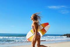 Deporte de agua extremo El practicar surf Muchacha con el funcionamiento de la playa de la tabla hawaiana Fotos de archivo
