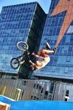 Deporte de BMX que salta en un fondo de la ciudad El Biking como deporte del extremo y de la diversión Fotos de archivo