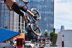 Deporte de BMX que salta en un fondo de la ciudad El Biking como deporte del extremo y de la diversión Imágenes de archivo libres de regalías