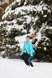 Deporte de invierno, muchacha que salta en nieve Fotografía de archivo