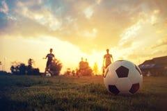 Deporte de la acción de la silueta al aire libre de un grupo de niños que se divierten que juega al fútbol del fútbol para el eje imagen de archivo