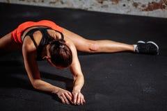 Deporte de la mujer que estira en gimnasio con la pared de ladrillo y las esteras negras imágenes de archivo libres de regalías