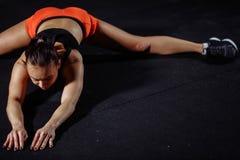 Deporte de la mujer que estira en gimnasio con la pared de ladrillo y las esteras negras foto de archivo