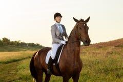 Deporte ecuestre El caballo de montar a caballo de la mujer joven en doma avanzó la prueba imagen de archivo