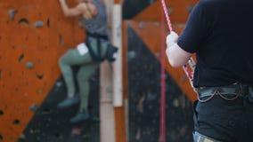 Deporte extremo, bouldering Un coche ayuda a la mujer a ir abajo de la pared metrajes