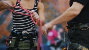 Deporte extremo, bouldering Una mujer implica las cuerdas de la protecci?n para subir bajo instrucciones del coche almacen de video