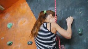Deporte extremo, bouldering Una mujer joven que sube para arriba almacen de video