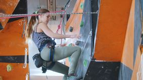 Deporte extremo, bouldering Una mujer joven que sube para arriba, pidiendo una ayuda y bajando almacen de video