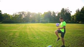 Deporte, fútbol y gente - jugador de fútbol que juega y que hace juegos malabares con la bola en campo almacen de metraje de vídeo