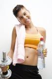 Deporte, gimnasio, muchacha que sostiene el peso y la botella de agua Fotos de archivo libres de regalías