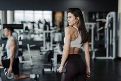 Deporte La mujer atl?tica de la aptitud que bombea para arriba muscles con pesas de gimnasia Muchacha atractiva morena de la apti imagenes de archivo