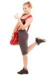 Deporte Muchacha deportiva de la aptitud con el bolso del gimnasio que muestra el pulgar para arriba Fotos de archivo libres de regalías