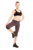 Deporte muchacha rubia deportiva de la aptitud que estira la pierna aislada Imagen de archivo libre de regalías