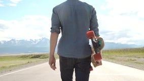 Deporte, ocio, gente y concepto adolescente - hombre joven o adolescente sonriente con longboard en el camino de la montaña metrajes