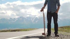 Deporte, ocio, gente y concepto adolescente - hombre joven o adolescente sonriente con longboard en el camino de la montaña almacen de metraje de vídeo